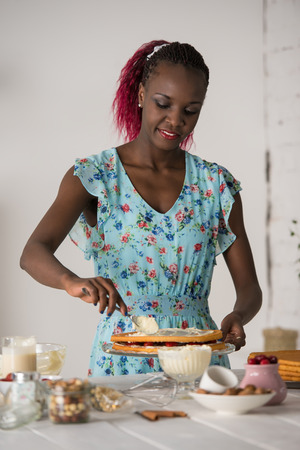 Beautiful young african woman cooking cake at kitchen photo