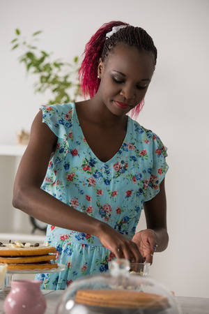 culinary skills: Beautiful young african woman cooking cake at kitchen