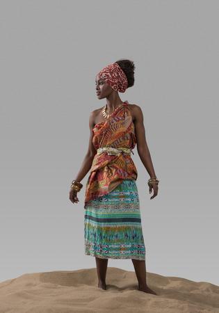 mannequin africain: Attractive jeune africaine mannequin debout sur le sable sur le gris studio de fond Banque d'images