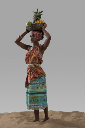 Attractive young african woman carrying fruits on sand on gray studio background
