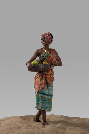 women posing: Attractive young african woman carrying fruits on sand on gray studio background