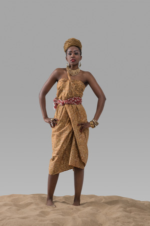 traditional dress: Attractive young African fashion model standing on sand on gray studio background Stock Photo