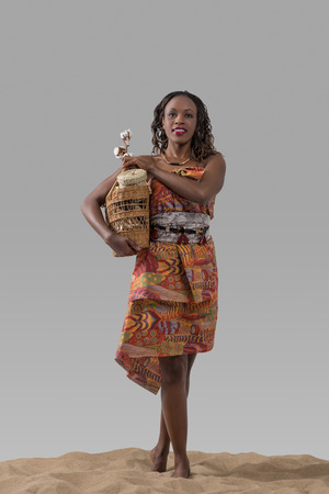 african basket: Attractive young african woman carrying basket with cotton and goods on sand on gray studio background Stock Photo