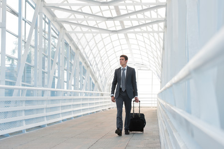 Businessman walking in urban environment of airport with suitcase