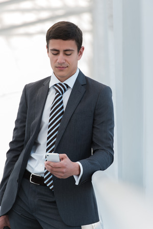 40 years old man: Businessman standing inside modern office building looking on a mobile phone