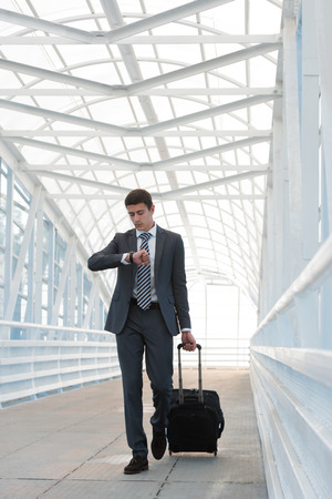 go inside: Businessman walking in urban environment of airport with suitcase