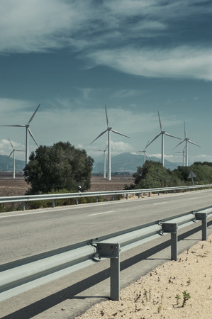 generate: Modern windmills generate electric power along country road