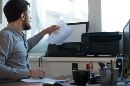 busy beard: Handsome businessman scanning and printing document in office