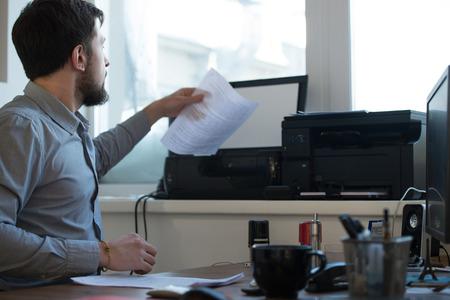 Knappe zakenman scannen en afdrukken document in kantoor Stockfoto