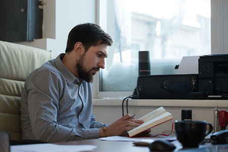 busy beard: Handsome businessman planning his day in office Stock Photo