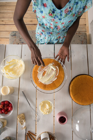 culinary skills: Beautiful young african woman cooking cake at kitchen. Top view Stock Photo