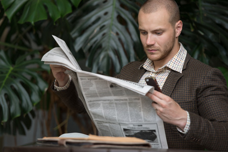 well read: Businessman reading newspaper on chair at office building hall or cafe Stock Photo