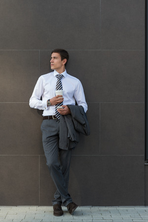 businessman waiting call: Businessman Leaning on Modern Office Building Wall With Coffee Using Mobile Phone