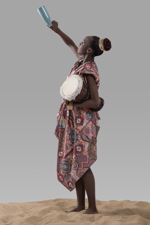 poor african: Attractive young african woman holding traditional drum and jug on sand on gray studio background