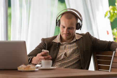 Business man resting at cafe and listening music using vintage headphones Imagens