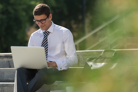 Man with laptop at summer park on bright day Standard-Bild