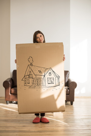 relocating: Mortgage and credit concept. Young woman relocating to new home and planning future