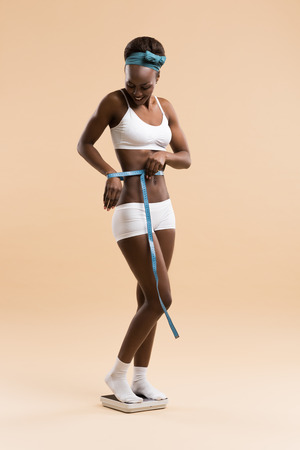 weightloss: African woman standing on scale measuring waist with tape celebrating weightloss and a healthy fit body Stock Photo