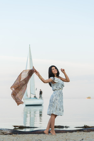 feeling up: Free woman enjoying freedom feeling happy at beach at morning. Beautiful serene woman and welcoming yacht and sailor with arms opened outstretched up. Hispanic Caucasian female model Stock Photo