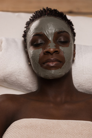 mud woman: African beauty woman getting mud mask at spa Stock Photo