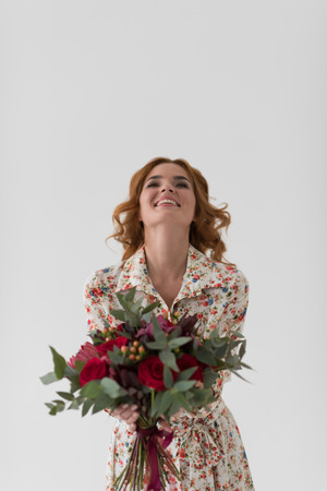 Beautiful woman with flower bouquet dancing photo