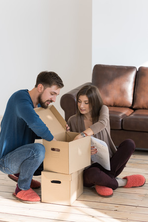 self assembly: Happy young couple putting together self assembly furniture as they move into their new house. Stock Photo