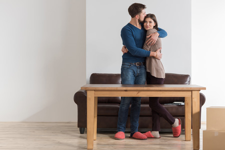 Side view of happy young couple embracing in living room of new home