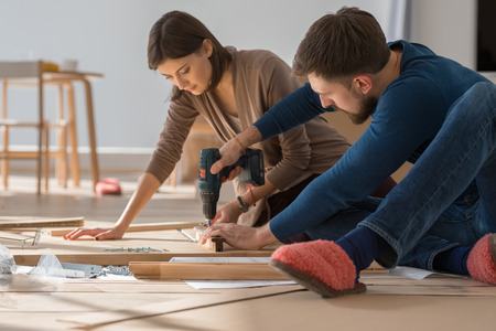 Happy young couple putting together self assembly furniture as they move into their new house. Stockfoto