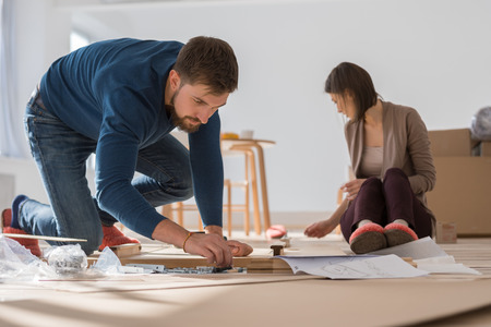 Happy young couple putting together self assembly furniture as they move into their new house. Zdjęcie Seryjne