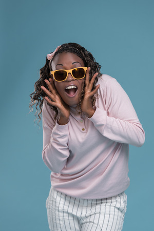 expressing: African woman wearing sunglasses and expressing positivity