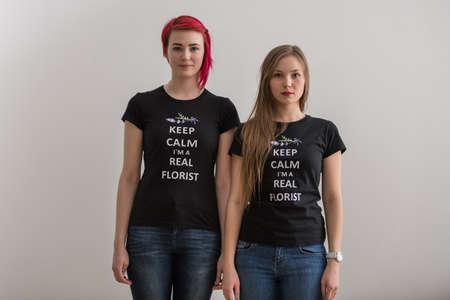 chicas divirtiendose: Dos chicas positivas j�venes se divierten juntos delante de la c�mara en la pared blanca