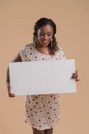 writable: Portrait of cute african woman posing - holding blank copyspace sign