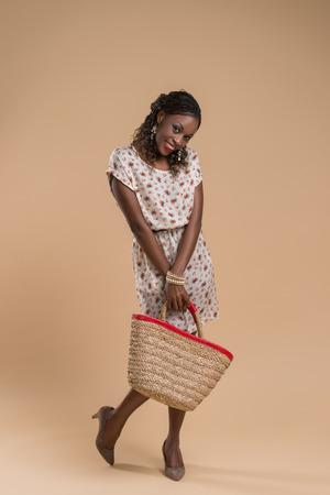mannequin africain: Portrait de jolie femme posant africain - debout avec sac de paille Banque d'images