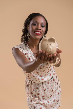 moneybox: Portrait of cute african woman posing - holding piggy moneybox