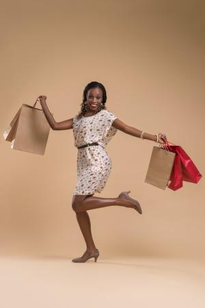 mannequin africain: Portrait de jolie femme africaine pose - du shopping avec des sacs en papier pleine portrait de longueur Banque d'images