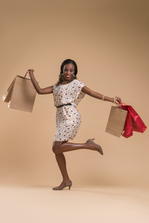 black fashion model: Portrait of cute african woman posing - shopping with paper bags full length portrait