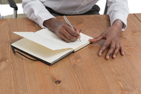 Afrikaanse zakelijke vrouw zit op haar bureau en planning op een witte achtergrond Stockfoto