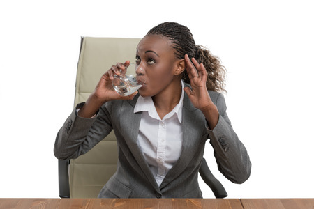 drinking water: African business woman sitting at her desk and drinking water isolated on white background