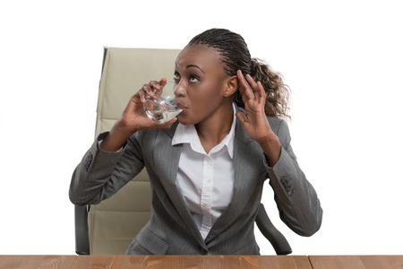 tomando agua: Las empresas africanas mujer sentada en su escritorio y agua potable aisladas sobre fondo blanco