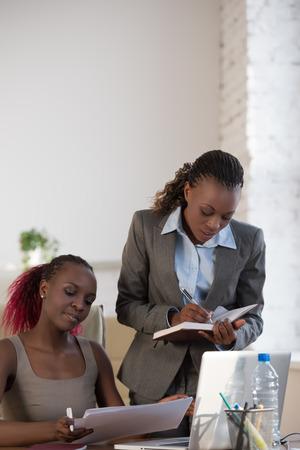 ejecutivo en oficina: Mujer de negocios africana que trabaja con la computadora portátil y su colega