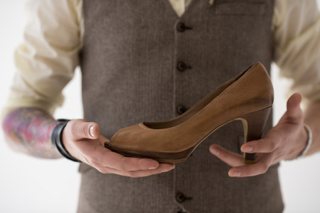 cinderella shoes: Closeup portrait of modern groom holding shoe of his bride