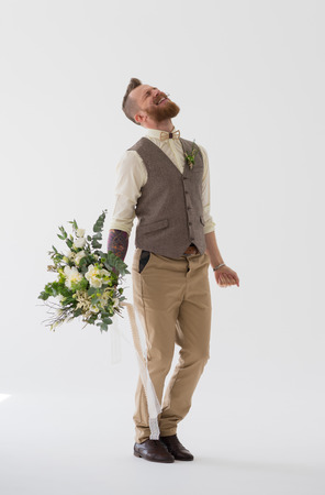 Full length portrait of modern groom dancing and jumping with wedding bouquet photo