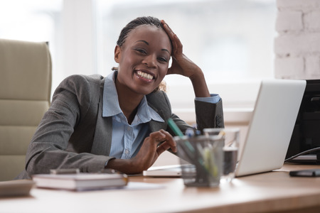 working hard: Thinking businesswoman in suit sitting at workplace and working hard with laptop