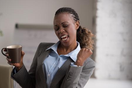 celebration: Szczery obraz businesswoman picia kawy podczas pracy w biurze. Selektywne fokus.