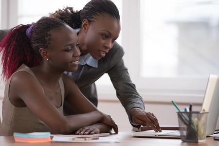 Mujer de negocios africana que trabaja con la computadora portátil y su colega