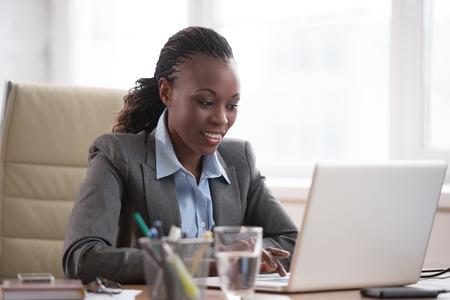 trabajando duro: Pensando de negocios en traje sentado en el lugar de trabajo y trabajando duro con el port�til