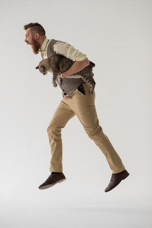 full length: Full length portrait of modern groom jumping with his cat
