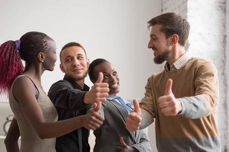 group cooperation: Cheerful business group giving thumbs up Stock Photo