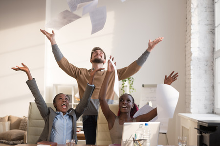 Business people excited happy smile, throwing up papers, documents fly in air, businesspeople sitting at office desk hold hands arms up, success team concept