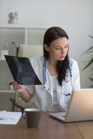 general practice: Medical doctor looking at xray of patient elbow at office Stock Photo